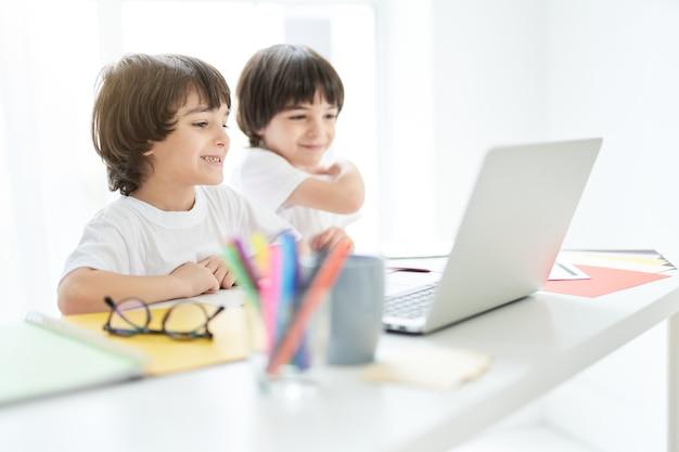 Ładny łaciński chłopiec wyglądający wesoło, siedzący z bratem przy stole z laptopem na nim. dwoje małych dzieci ma lekcję online w domu. edukacja na odległość podczas koncepcji blokady