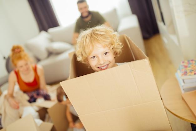 Ładny ładny blond chłopiec patrząc z pudełka