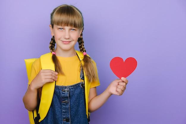 Ładny ładny blond uczennica trzyma małe czerwone serce z papieru, ubrany w żółty plecak, na białym tle nad pastelowym fioletowym kolorem tła z miejscem na kopię dla treści promocyjnych. miłość i powrót do koncepcji szkoły