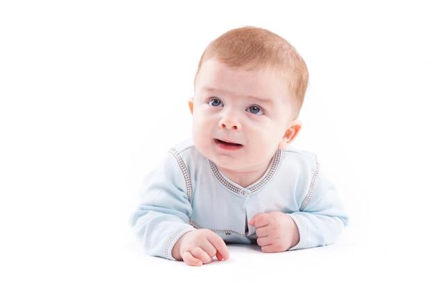 Ładny ładny mały chłopiec w niebieskiej koszuli leży na brzuchu