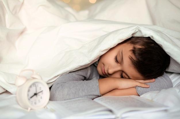 Ładny maluch chłopiec śpi z książką pod białym kocem.
