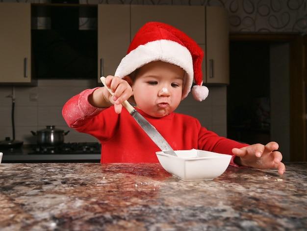 Ładny maluch chłopiec w świątecznym kapeluszu do gotowania