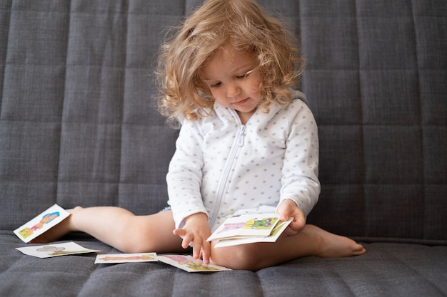 Ładny maluch dziewczyna bawić się kartami wczesnego rozwoju, siedząc na kanapie. kolorowe karty flash dla dzieci. zabawki dla małych dzieci. dziecko z edukacyjną zabawką.
