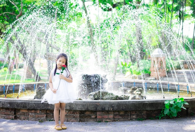 Ładny mały asian dziewczyna w białej sukni trzyma czerwoną różę w parku