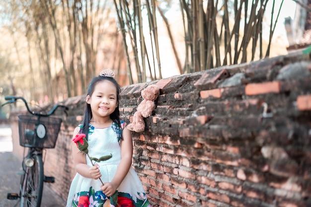 Ładny mały asian dziewczyna w sukience trzyma czerwoną różę w parku