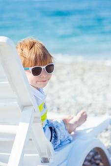 Ładny mały blond chłopiec w okularach przeciwsłonecznych siedzi na leżaku na wybrzeżu oceanu