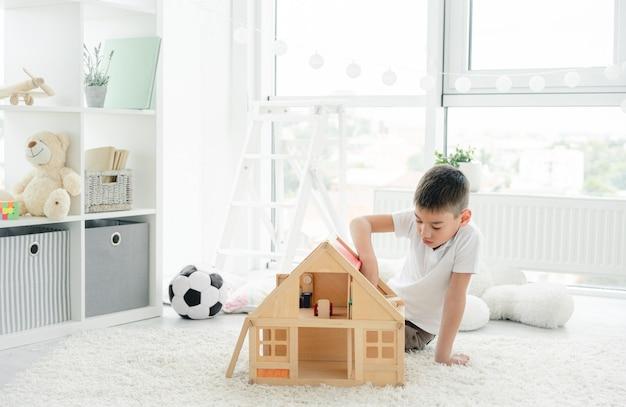 Ładny mały chłopiec bawi się domkiem dla lalek