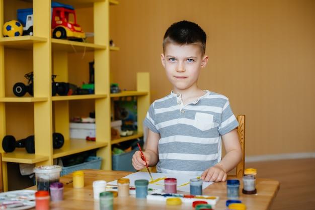 Ładny mały chłopiec bawi się i maluje w swoim pokoju. rekreacja i rozrywka. zostań w domu.