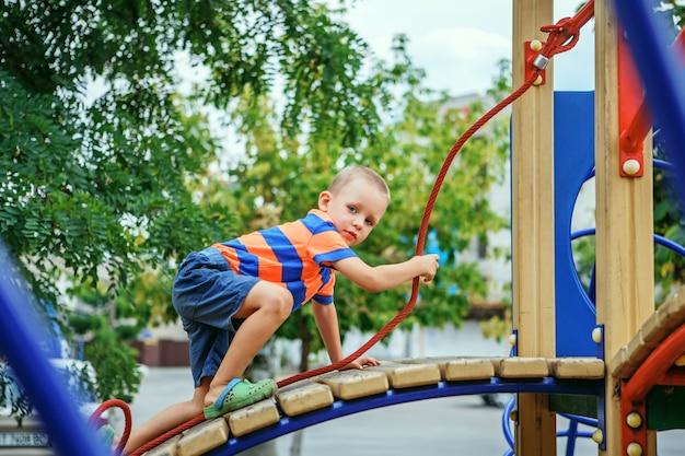 Ładny mały chłopiec bawi się na placu zabaw w lecie w mieście