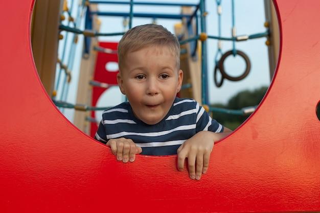 Ładny mały chłopiec bawi się na placu zabaw