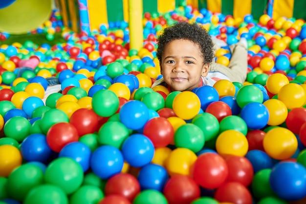 Ładny mały chłopiec bawi się w ballpit