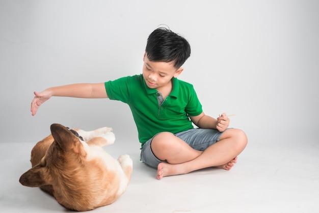 Ładny mały chłopiec bawi się z psem w domu