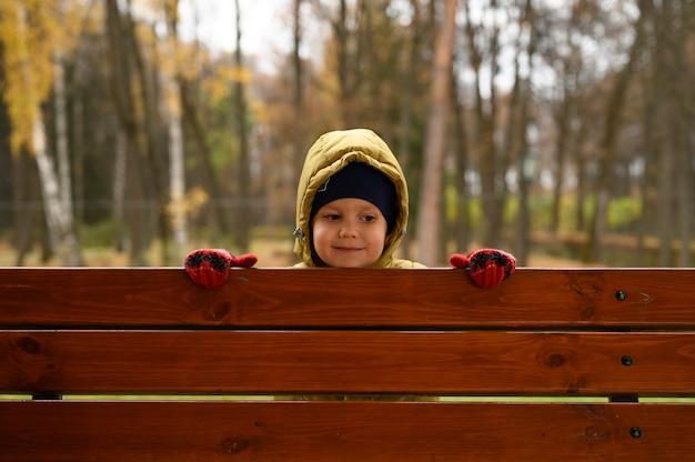 Ładny mały chłopiec bawi się z rodziną w jesiennym parku w słoneczny jesienny dzień