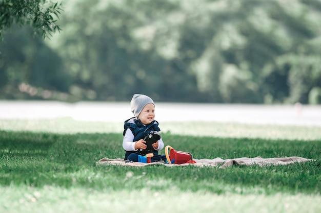 Ładny mały chłopiec bawi się zabawkami, siedząc na trawniku w parku