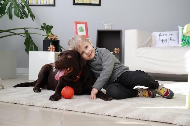 Ładny mały chłopiec bawi się zabawnym psem w domu