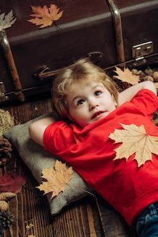 Ładny mały chłopiec dziecko szykują się do jesieni. blond mały chłopiec odpoczywa z liściem na brzuchu leży