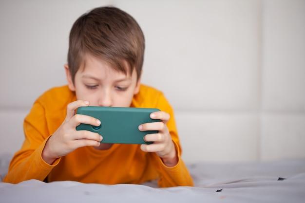 Ładny mały chłopiec gra w gry wideo na swoim smartfonie