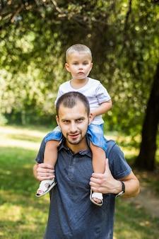 Ładny mały chłopiec i jego przystojny młody tata czekają i uśmiechają się, odpoczywając w parku