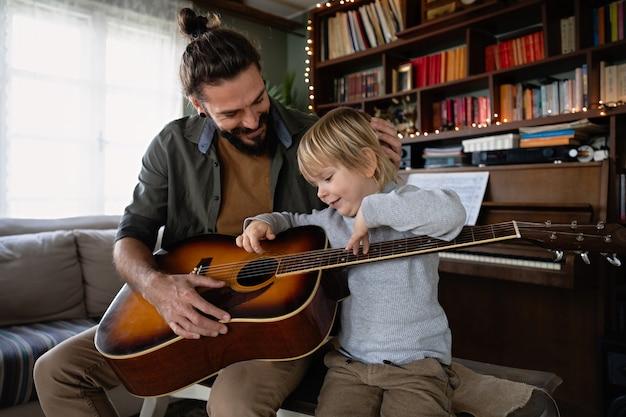 Ładny mały chłopiec i jego przystojny ojciec grają na gitarze i uśmiechają się w domu. koncepcja miłości rodzinnej
