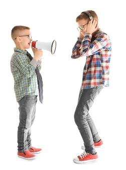 Ładny mały chłopiec ignoruje swojego przyjaciela z megafonem, na białym tle