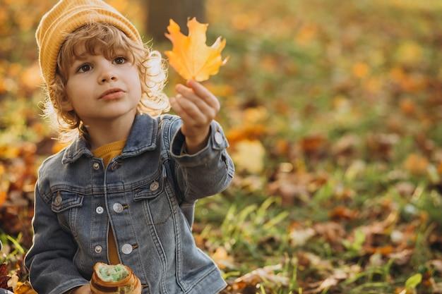 Ładny mały chłopiec jedzenie rogalika w parku
