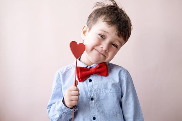 Ładny mały chłopiec kaukaski w muszka z czerwonym sercem na kij trzymać róża na różowym tle. walentynki.