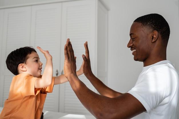 Ładny mały chłopiec klaszcząc w dłonie z tatą