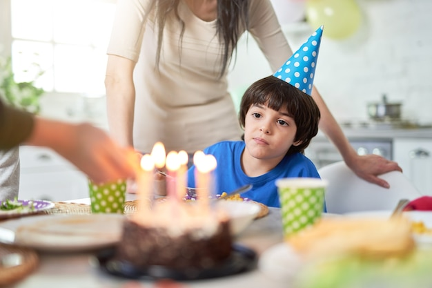 Ładny mały chłopiec latynoamerykański w czapce birtday patrząc na tort urodzinowy podczas obchodów urodzin z rodziną w domu. dzieci, koncepcja uroczystości