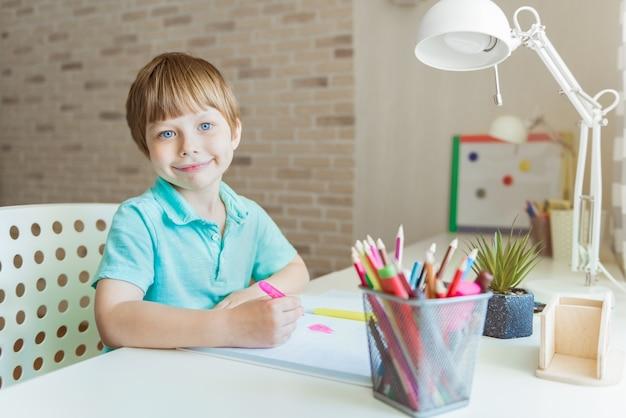 Ładny mały chłopiec malowanie kredkami w domu