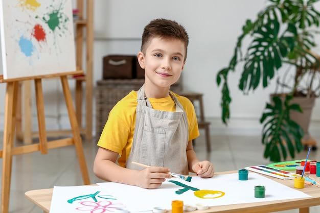 Ładny mały chłopiec malowanie w domu