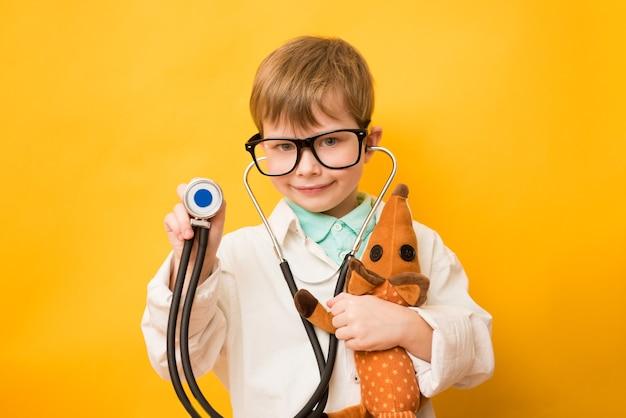 Ładny mały chłopiec nosić medyczne jednolite okulary trzymając stetoskop grający lekarza