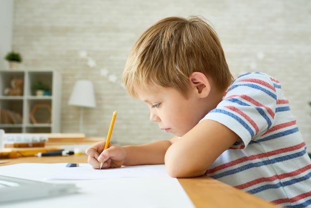 Ładny mały chłopiec odrabiania lekcji
