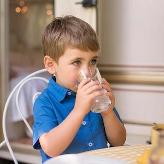 Ładny mały chłopiec pije lemoniadę
