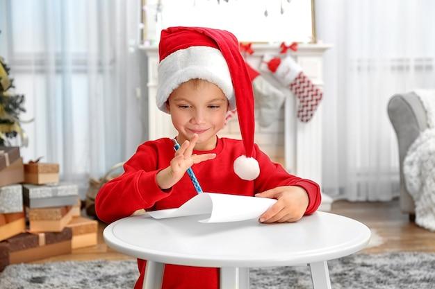 Ładny mały chłopiec pisze list do świętego mikołaja przy stole