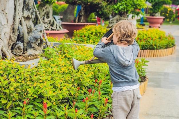 Ładny mały chłopiec podlewanie kwiatów konewka