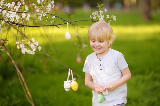 Ładny mały chłopiec poluje na pisanki na gałęzi kwitnących drzew.