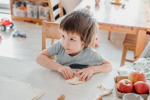Ładny mały chłopiec przygotowuje ciasto do ciasta w kuchni