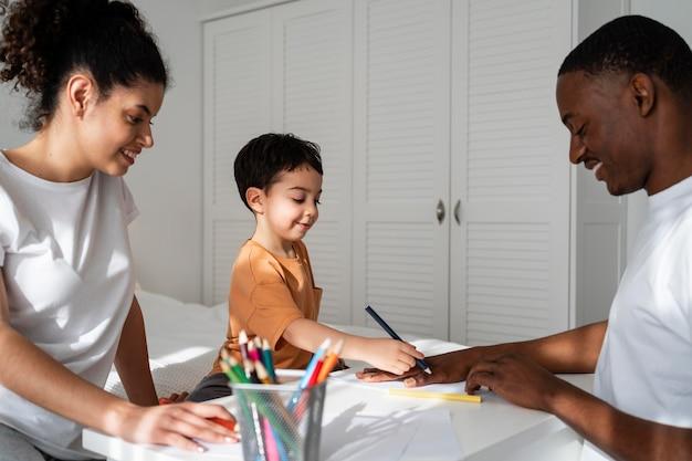 Ładny mały chłopiec rysuje jego ojciec rękę na papierze, uśmiechając się