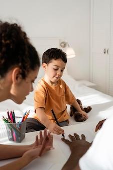 Ładny mały chłopiec rysuje rękę ojca na papierze