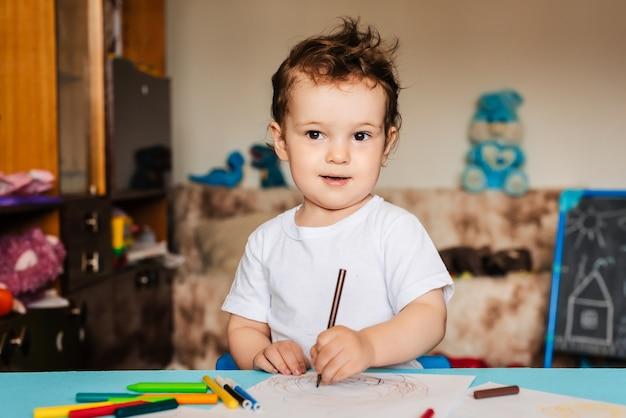 Ładny mały chłopiec rysuje w swoim szkicowniku kolorowymi kredkami
