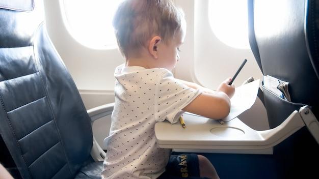 Ładny mały chłopiec rysunek obraz z ołówkami podczas lotu samolotem.