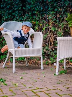 Ładny mały chłopiec siedzi na białym krześle z zielonymi roślinami