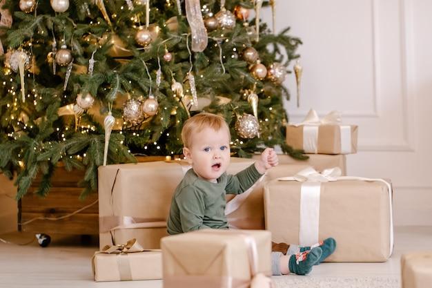 Ładny mały chłopiec siedzi pod choinką z pudełkiem.