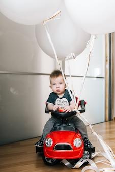 Ładny mały chłopiec siedzi w czerwonym samochodzie z dużymi białymi balonami, szczęśliwe dzieciństwo, gry dla dzieci, kochanie