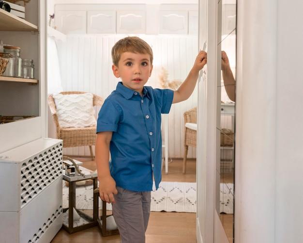 Ładny mały chłopiec stojący w przyczepie kempingowej