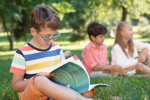 Ładny mały chłopiec studiuje na świeżym powietrzu z przyjaciółmi