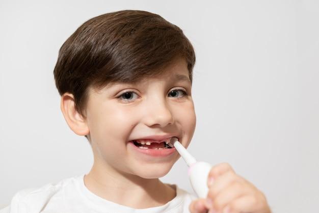 Ładny mały chłopiec szczotkowanie zębów, na białym tle