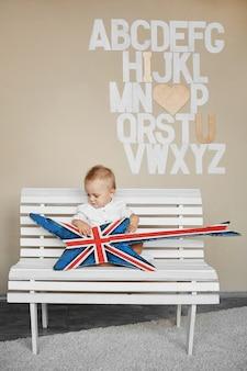 Ładny mały chłopiec w białej koszuli siedzi z gitarą basową na białej ławce w pomieszczeniu przy ścianie z alfabetem