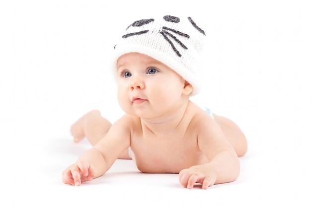 Ładny mały chłopiec w białej pieluchy i kapelusz kota