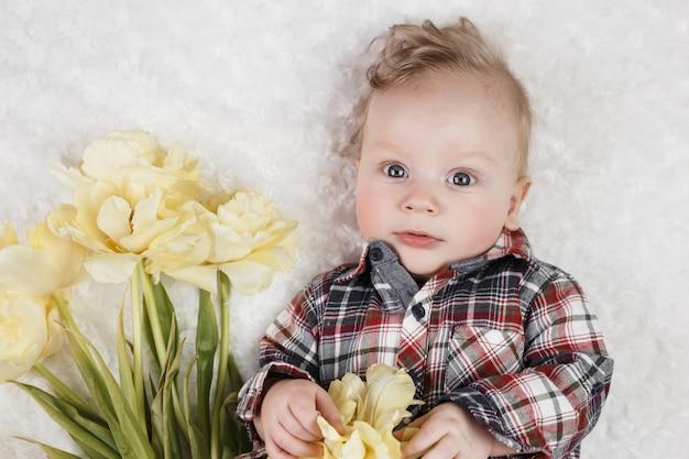 Ładny mały chłopiec w kraciastej koszuli trzyma bukiet żółtych tulipanów